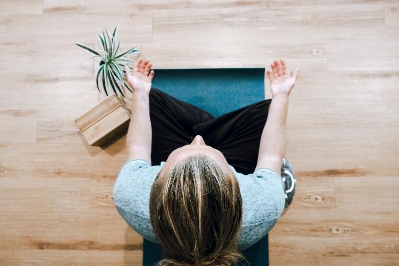 femme en tailleur médite sur un tapis